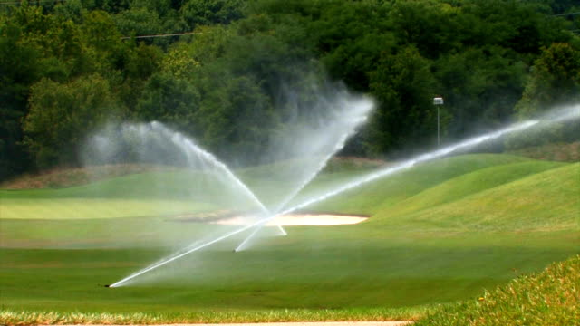 sprinklers on a golf course - green golf course stock videos and b-roll footage