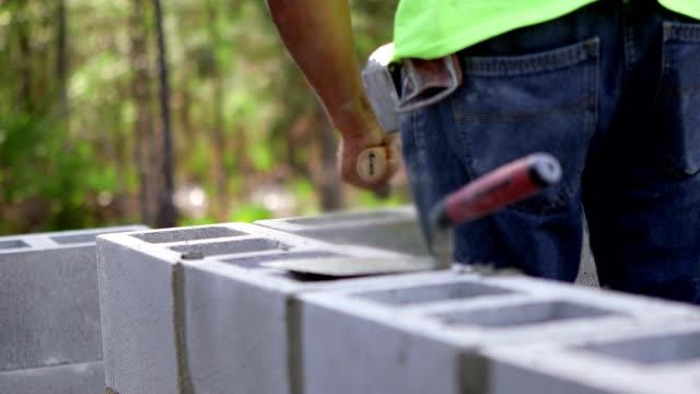 vidéos et rushes de travailleur de la construction de maisons, cendre - parpaing