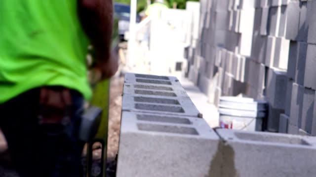 vidéos et rushes de travailleurs de la construction de maisons, cendre - parpaing