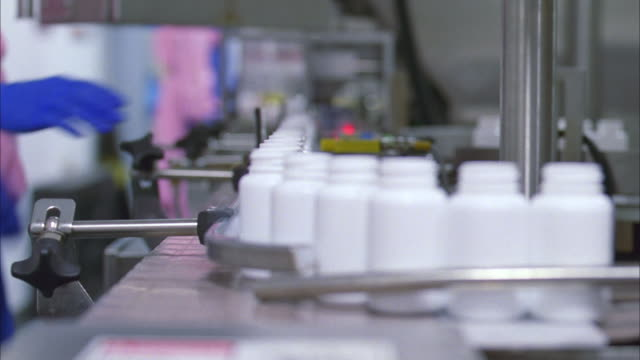 pill/capsule bottles move along assembly line - pharmaceutical factory stock videos & royalty-free footage