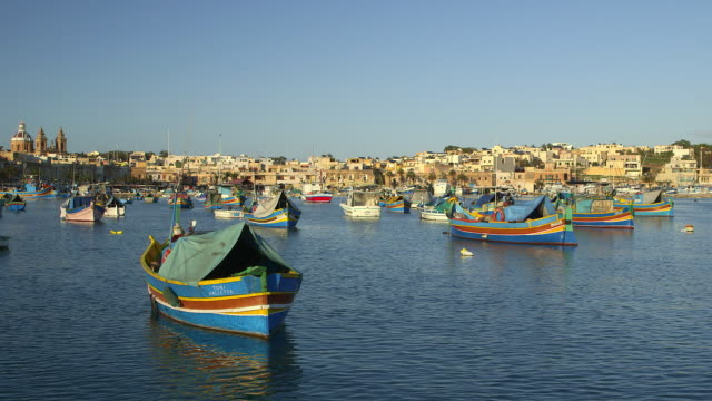 multi coloured fishing boats and town - malta stock videos & royalty-free footage