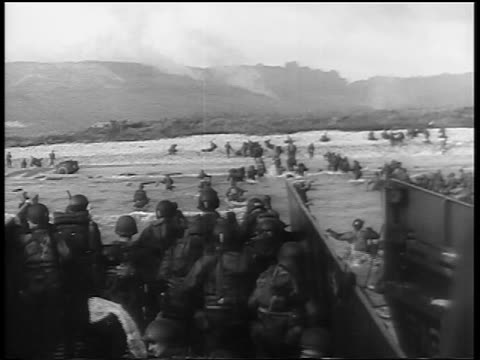 view soldiers on landing craft walking thru water toward normandy beach / dday - d day stock videos & royalty-free footage