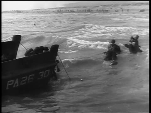 high angle soldiers exiting landing craft into water walking toward normandy beach / d-day - d day stock videos & royalty-free footage