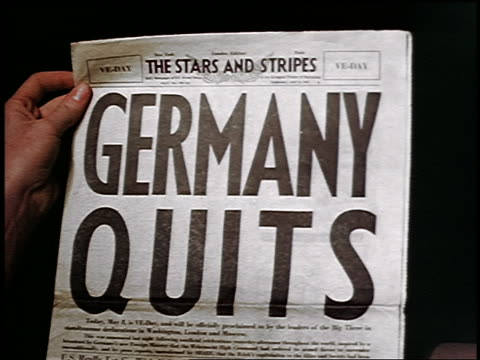 1945 close up man's hand holding newspaper with headline Germany Quits