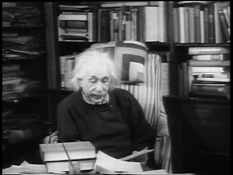 Albert Einstein sitting in chair reading aloud