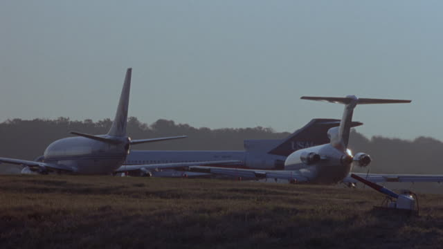 vídeos de stock, filmes e b-roll de medium angle of rear of two commercial airliner airplanes on runway waiting for taxiing. us air commercial airliner taxies to left. - medium group of objects