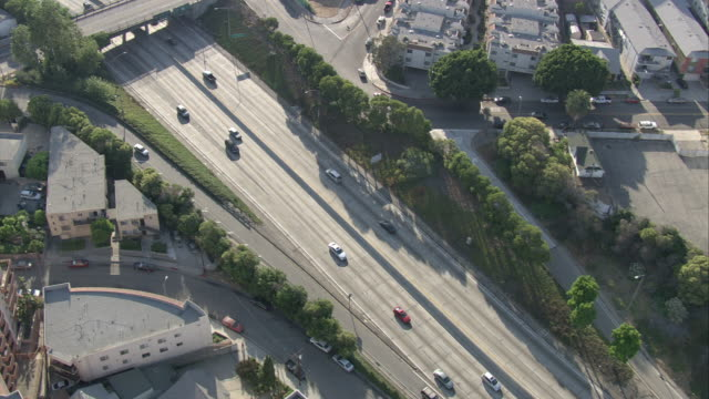 AERIAL OF 5 FREEWAY OR HIGHWAY OUTSIDE OF DOWNTOWN LOS ANGELES. LIGHT TRAFFIC. CAMERA FOLLOW SILVER MERCEDES CAR ON FREEWAY. CARS DRIVES INTO AND THROUGH TUNNELS. CAMERA MOVING TOWARDS SAN GABRIEL VALLEY OR PASADENA.