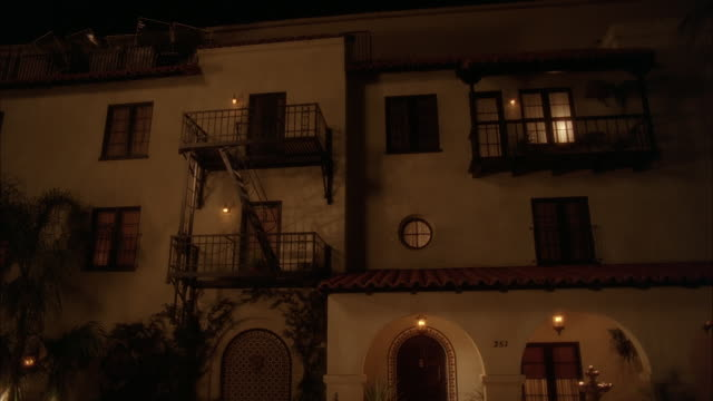 WIDE ANGLE OF THREE STORY SPANISH-STYLE APARTMENT BUILDING. MIDDLE CLASS. DAY-NIGHT MATCHING SHOTS.