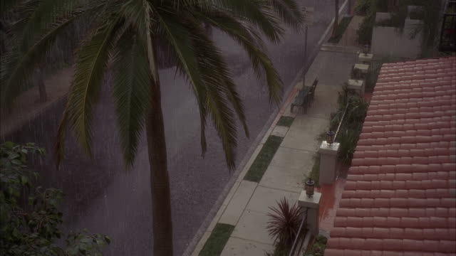 high angle down of spanish style roof over apartment building or house during rain storm. residential area or neighborhood. city street in fg. palm trees.  day-night matching shots. - southern california stock videos & royalty-free footage