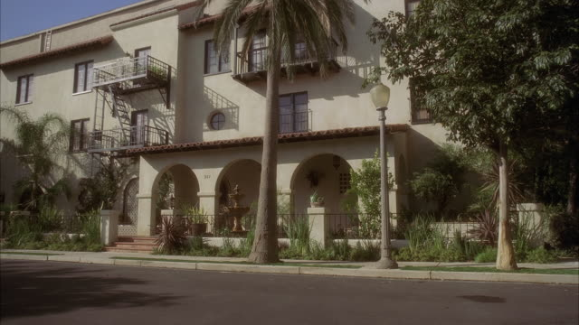 WIDE ANGLE OF MULTI-STORY SPANISH STYLE APARTMENT BUILDING. BALCONIES OR FIRE ESCAPES VISIBLE. CARS DRIVE BY ON STREET. FOUNTAIN AT ARCHED ENTRYWAY TO BUILDING. RESIDENTIAL AREA OR NEIGHBORHOOD. PALM TREES.