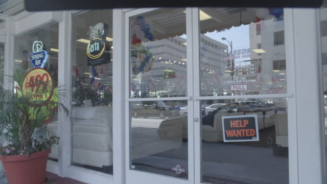 medium angle of the front door of a leeds mattress store with a help wanted sign in the front door or storefront. could be used to show the job market or the economy. - help wanted sign stock videos and b-roll footage