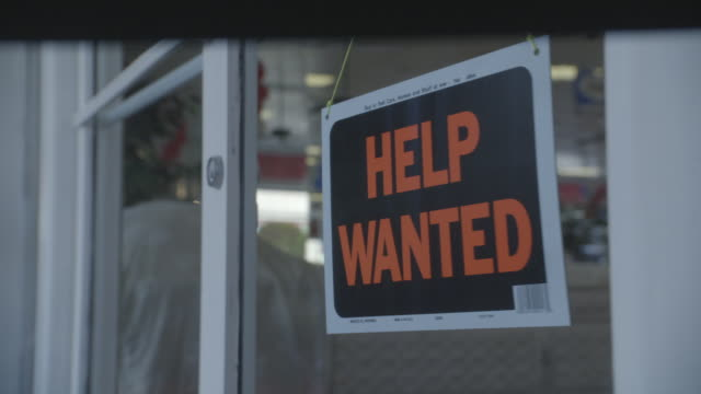 close angle of the front door of a leeds mattress store with a help wanted sign in the front door or storefront. a hand turns the sign so that it faces forward. could be used to show the job market or the economy. - help wanted sign stock videos and b-roll footage