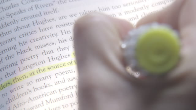 CLOSE ANGLE OF A HAND BRINGING A HIGHLIGHTER TO A PAGE OF A BOOK. COULD BE USED FOR STUDYING.