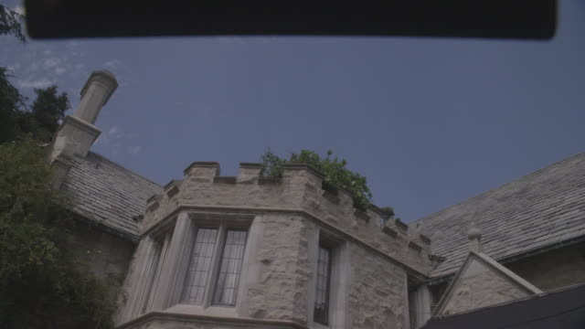 up angle of the playboy mansion as a flock of pigeons fly from the roof. tudor style, upper class house. beverly hills. slate roof. - playboy mansion stock videos & royalty-free footage