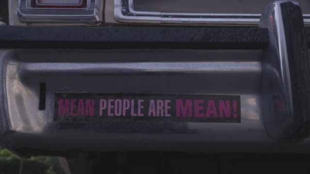stockvideo's en b-roll-footage met close angle of a bumper sticker that reads mean people are mean! a station wagon car drives away from the camera. the car backfires as it pulls away. - bumper
