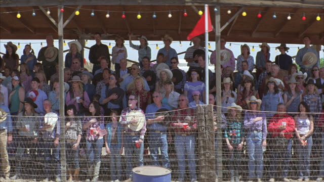 wide angle of crowd or spectators wearing cowboy hats sitting in bleachers behind chicken wire fence. people stand with hands over hearts. could be national anthem. rodeo. decorative lights and flags. - 1 minute or greater stock videos & royalty-free footage