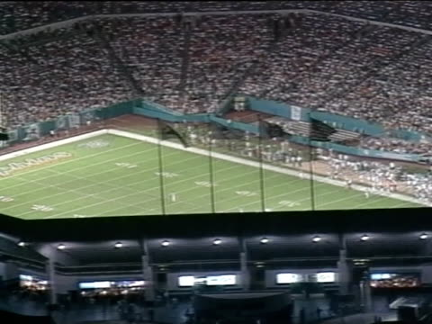 AERIAL NIGHT High Altitude Joe Robbie Stadium sports complex field in football configuration seating purple players near End Zone