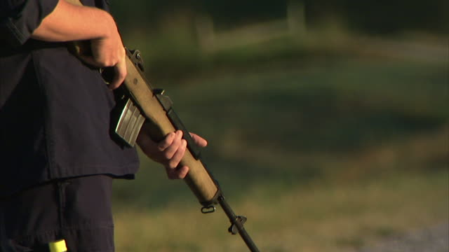 Young adult male prison guard torso hands holding rifle in pointing down position body leaning forward spitting Correctional officer maximum security...