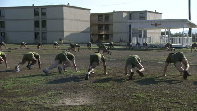 Male Marines exercising in large circle outside w/ Drill Instructor working in center ZO XWS Marines exercising in pushup position alternating legs...