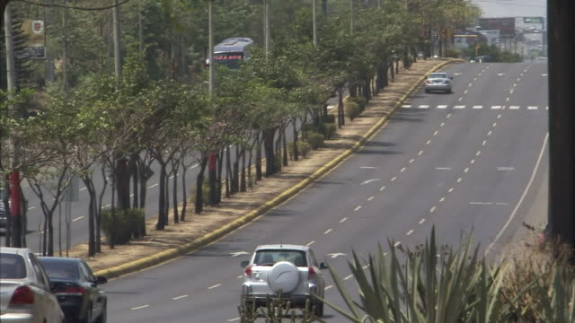 multi-lane highway w/ divider w/ trees, various vehicles driving in both directions, cars, buses, motorists. - managua stock videos & royalty-free footage