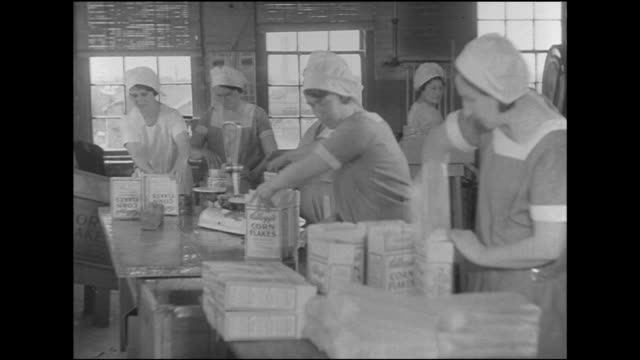 vídeos y material grabado en eventos de stock de hd *angled ws women working by hand in production line at table placing paper lining in cereal boxes filling w/ corn flakes weighing box then sealing... - cereal plant