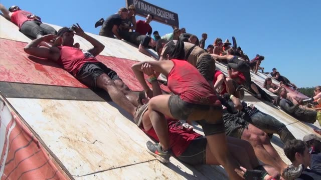 obstacle racers help each other through the course over structures and through mud pits they form a human ladder to get to top of structure - tough mudder stock videos and b-roll footage
