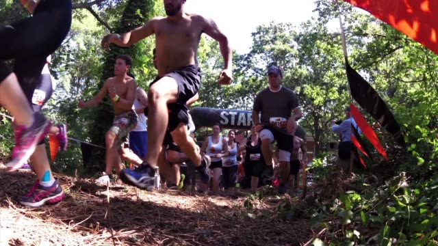 obstacle racers start event up hill to course camera on ground - obstacle course stock videos & royalty-free footage