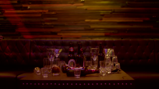 vidéos et rushes de close angle of empty glasses and beer bottles on table at nightclub or bar. - demi finale