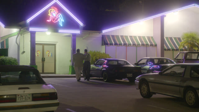 MEDIUM ANGLE OF STRIP CLUB. CARS IN PARKING LOT. MEN WALK IN. NEON COWGIRL SIGN.