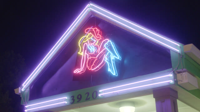 MEDIUM ANGLE OF NEON COWGIRL SIGN.