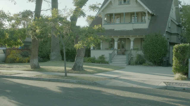medium angle of car, station wagon arriving at a two-story middle class house. - zweistöckiges wohnhaus stock-videos und b-roll-filmmaterial