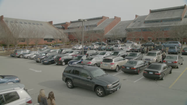 medium angle of cars in parking lot of brick buildings. could be community center or community college. - community college stock videos & royalty-free footage