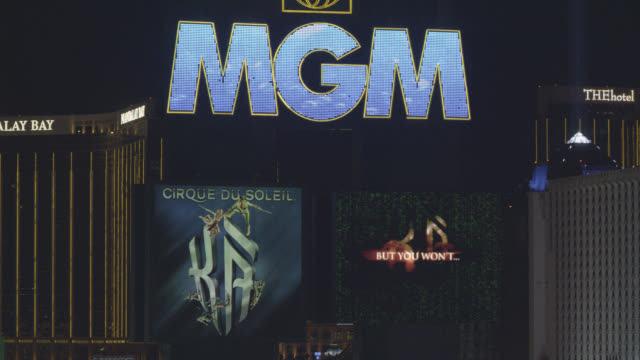 PAN LEFT TO RIGHT CLOSE ANGLE TO MGM GRAND NEON SIGN IN FG.  LUXOR, MADNALAY BAY, AND EXCALIBUR HOTEL AND CASINOS PARTIALLY VISIBLE IN BG.