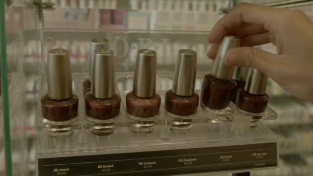 PAN RIGHT TO LEFT OF HAND SELECTING NAIL POLISHES.