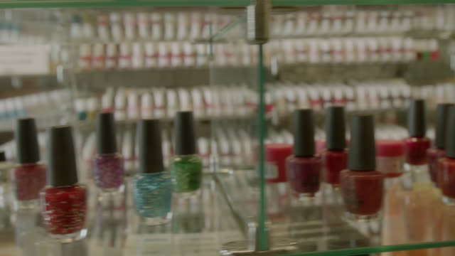 vídeos de stock e filmes b-roll de pan right to left of hand selecting nail polishes. - manicure