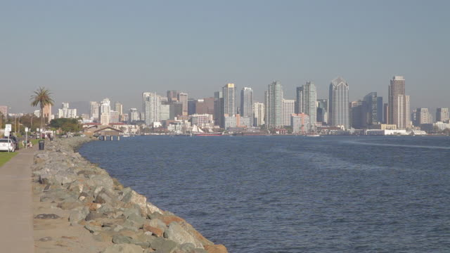 WIDE ANGLE OF SKYSCRAPERS AND HIGH RISE OFFICE OR APARTMENT BUILDINGS IN SAN DIEGO CITY SKYLINE. SAILBOATS IN HARBOR.