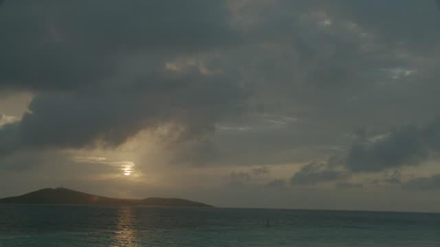 vídeos de stock e filmes b-roll de wide angle of sun setting. island coastline and ocean. cloudy sky. - coastline