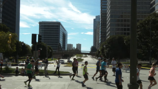 wide angle side view of runners running la marathon on santa monica blvd. - santa monica blvd stock videos & royalty-free footage