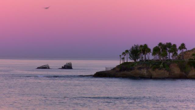 WIDE ANGLE OF COVE IN LAGUNA BEACH. PURPLE SKY.