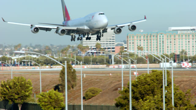 PAN LEFT TO RIGHT OF CARGO PLANE LANDING AT LAX. RUNWAY VISIBLE.