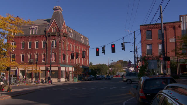 WIDE ANGLE OF MAIN STREET INTERSECTION IN SMALL TOWN. BRICK BUILDING HOTELS OR SHOPS VISIBLE.