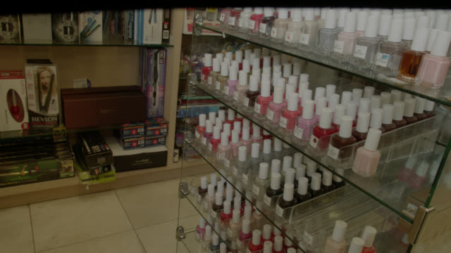 vídeos de stock e filmes b-roll de zoom in on nail polishes on display. - manicure