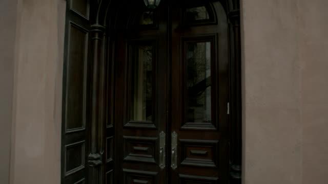 ZOOM IN ON FRONT DOOR OF APARTMENT BUILDING.