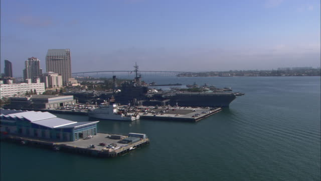 vídeos de stock e filmes b-roll de aerial of uss midway, aircraft carrier and navy ship. city skyline in bg. - uss midway
