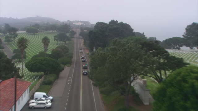 aerial of police cars following, chasing pickup truck towing a boat on two-lane road cemetery or graveyard. fort rosecrans national cemetery, point loma. - cars in a row stock videos & royalty-free footage