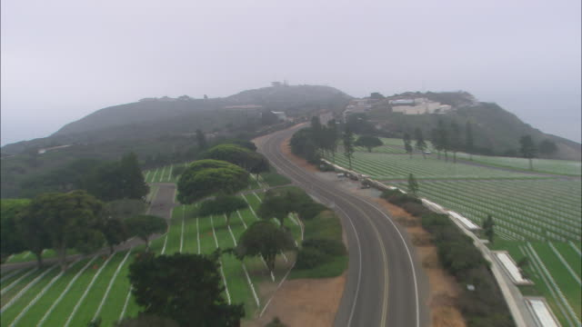 aerial of police cars following, chasing pickup truck towing a boat on two-lane road cemetery or graveyard. fort rosecrans national cemetery, point loma. - police boat stock videos and b-roll footage
