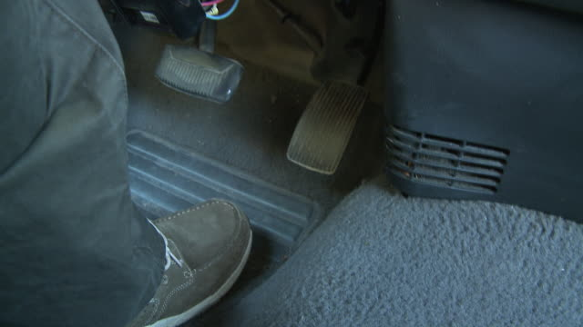 CLOSE ANGLE OF FOOT STEPPING ON GAS PEDAL WHILE DRIVING CAR. SERIES.
