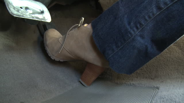 close angle of high-heeled shoe stepping on gas pedal and brake while driving car. series. - pedal stock videos & royalty-free footage