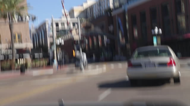 PAN LEFT TO RIGHT OF CAR DRIVING ON CITY STREET PAST BASEBALL STADIUM, PETCO PARK.