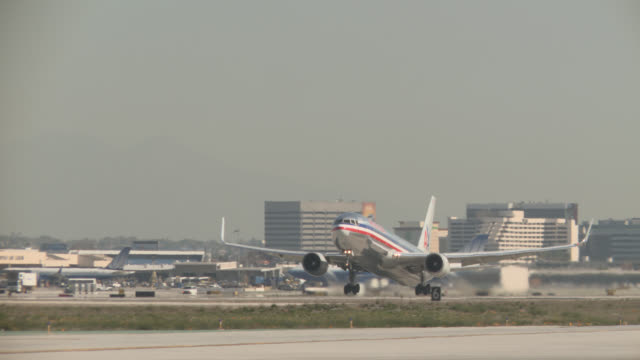 PAN RIGHT TO LEFT OF COMMERCIAL AIRLINER OR AIRPLANE TAKING OFF FROM RUNWAY. LOS ANGELES INTERNATIONAL AIRPORT.